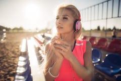 Retrato de una muchacha adolescente deportiva que descansa del ejercicio, escuchando la música con los auriculares, sonriendo al  Imagen de archivo