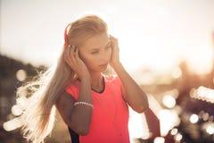 Retrato de una muchacha adolescente deportiva que descansa del ejercicio, usando escuchar la música con los auriculares, sonriend Imagen de archivo