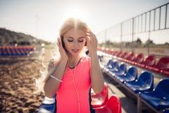 Retrato de una muchacha adolescente deportiva que descansa del ejercicio, usando escuchar la música con los auriculares, sonriend Fotos de archivo libres de regalías