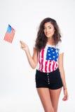 Retrato de una muchacha adolescente feliz que sostiene la bandera de los E.E.U.U. Imagen de archivo libre de regalías
