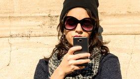 Retrato de una muchacha adolescente hermosa que mira su smartphone - filtro caliente Imagenes de archivo