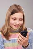 Retrato de una muchacha adolescente linda con el teléfono Imagen de archivo libre de regalías
