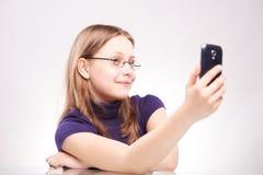 Retrato de una muchacha adolescente linda con el teléfono que toma el selfie Imagen de archivo libre de regalías