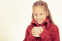 Retrato de una muchacha adolescente linda en el suéter rojo que sostiene una taza Fotos de archivo