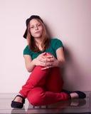 Retrato de una muchacha adolescente que se sienta en la tabla Imagen de archivo libre de regalías