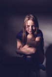 Retrato de una muchacha adolescente que se sienta en una silla en un cuarto oscuro, contr Fotografía de archivo libre de regalías