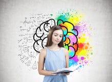 Retrato de una muchacha adolescente que sostiene un libro, cerebro Imagen de archivo
