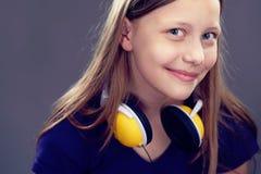 Retrato de una muchacha adolescente sonriente con los auriculares Imagen de archivo