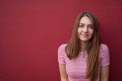Retrato de una muchacha adolescente sonriente en un fondo rojo Fotografía de archivo libre de regalías