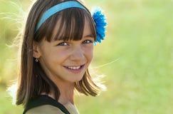 Retrato de una muchacha adolescente sonriente hermosa del aspecto europeo con la decoración en el pelo oscuro en un campo Foto de archivo libre de regalías