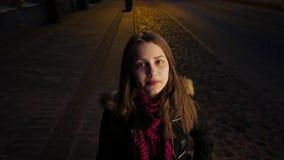 Retrato de una muchacha adolescente sonriente linda en una calle de la ciudad de la noche Riendo y divirtiéndose almacen de metraje de vídeo