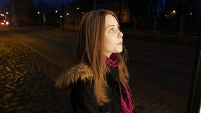 Retrato de una muchacha adolescente sonriente pensativa linda en una calle de la ciudad de la noche Mirada de la cartelera almacen de metraje de vídeo