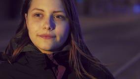 Retrato de una muchacha adolescente sonriente pensativa linda en una calle de la ciudad de la noche slowmo de 4K UHD almacen de video