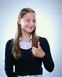 Retrato de una muchacha adolescente sonriente que muestra los pulgares para arriba Imágenes de archivo libres de regalías