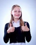 Retrato de una muchacha adolescente sonriente que muestra los pulgares para arriba Fotos de archivo