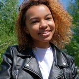 Retrato de una muchacha afroamericana negro-pelada hermosa en la calle en un fondo de árboles verdes Un mulato adolescente en un  Fotos de archivo