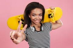 Retrato de una muchacha afroamericana sonriente del adolescente que sostiene el monopatín Fotografía de archivo