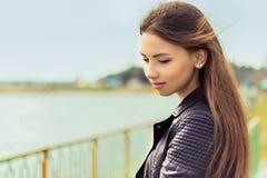 Retrato de una muchacha agraciada apacible elegante hermosa con el pelo oscuro que hace una pausa el lago Imágenes de archivo libres de regalías