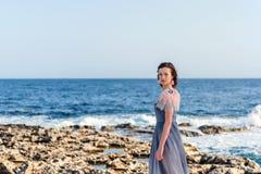 Retrato de una muchacha agraciada delgada joven en un vestido gris con las plumas rosadas con un mar azul brillante que rabia en  Foto de archivo