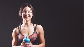 Retrato de una muchacha alegre atlética en el estudio en un fondo negro con una botella de agua almacen de video