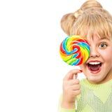 Retrato de una muchacha alegre con el caramelo en un fondo blanco Imagenes de archivo