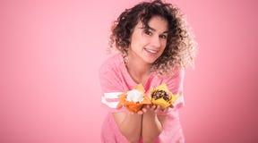 Retrato de una muchacha alegre con las magdalenas en sus manos foto de archivo libre de regalías