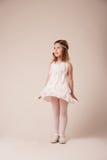 Retrato de una muchacha alegre hermosa en un vestido de las plumas blancas Foto de archivo libre de regalías
