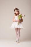 Retrato de una muchacha alegre hermosa en un vestido de las plumas blancas, con las flores en sus manos Fotos de archivo libres de regalías