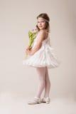 Retrato de una muchacha alegre hermosa en un vestido de las plumas blancas, con las flores en sus manos Imagenes de archivo