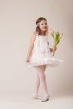 Retrato de una muchacha alegre hermosa en un vestido de las plumas blancas, con las flores en sus manos Fotografía de archivo