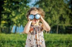 Retrato de una muchacha alegre que mira a través de los prismáticos Fotografía de archivo libre de regalías