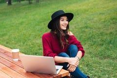 Retrato de una muchacha asiática bastante alegre que usa el ordenador portátil Fotografía de archivo libre de regalías