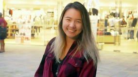 Retrato de una muchacha asiática del este sonriente hermosa En el fondo son las luces borrosas de un supermercado grande metrajes