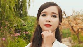 Retrato de una muchacha asiática vietnamita joven que mira la cámara Maquillaje fuerte almacen de metraje de vídeo