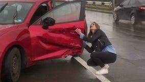 Retrato de una muchacha asustada cerca de su coche quebrado despu?s de un accidente en un camino mojado almacen de metraje de vídeo