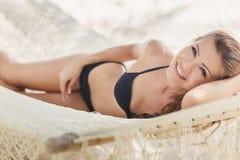 Retrato de una muchacha atractiva en un bikini que miente en una hamaca Imagenes de archivo