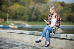 Retrato de una muchacha atractiva joven que se sienta en el puente Fotografía de archivo libre de regalías