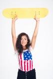 Retrato de una muchacha bastante adolescente que sostiene el monopatín Fotografía de archivo