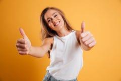 Retrato de una muchacha bastante alegre que muestra los pulgares para arriba Imágenes de archivo libres de regalías