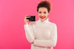 Retrato de una muchacha bastante alegre que sostiene la cámara de la foto Imagenes de archivo