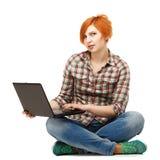 Retrato de una muchacha bastante pelirroja de los jóvenes con una sentada del ordenador portátil Imagenes de archivo