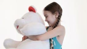 Retrato de una muchacha blanca linda con las coletas que abrazan con un peluche grande para referir un fondo blanco en el estudio almacen de video