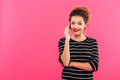 Retrato de una muchacha bonita alegre que habla en el teléfono móvil Fotos de archivo libres de regalías