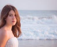 Retrato de una muchacha bonita con las olas oceánicas en el fondo Foto de archivo libre de regalías