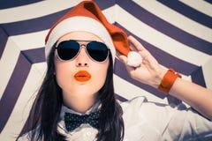 Retrato de una muchacha bonita en el sombrero y las gafas de sol de Santa Claus Fotos de archivo