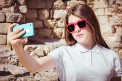 Retrato de una muchacha bonita en las gafas de sol que toman el autorretrato Imagen de archivo libre de regalías
