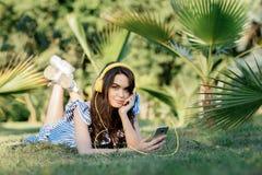 Retrato de una muchacha bonita en ropa del verano que escucha la música con los auriculares amarillos mientras que sostiene el te imagen de archivo