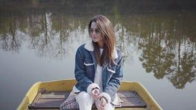 Retrato de una muchacha bonita en vidrios y de una chaqueta del dril de algodón que flota en un barco en un lago o un río La more almacen de video