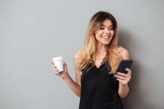 Retrato de una muchacha bonita feliz que sostiene la taza de café Imagenes de archivo