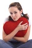 Retrato de una muchacha bonita que abraza un corazón rojo grande Imagen de archivo